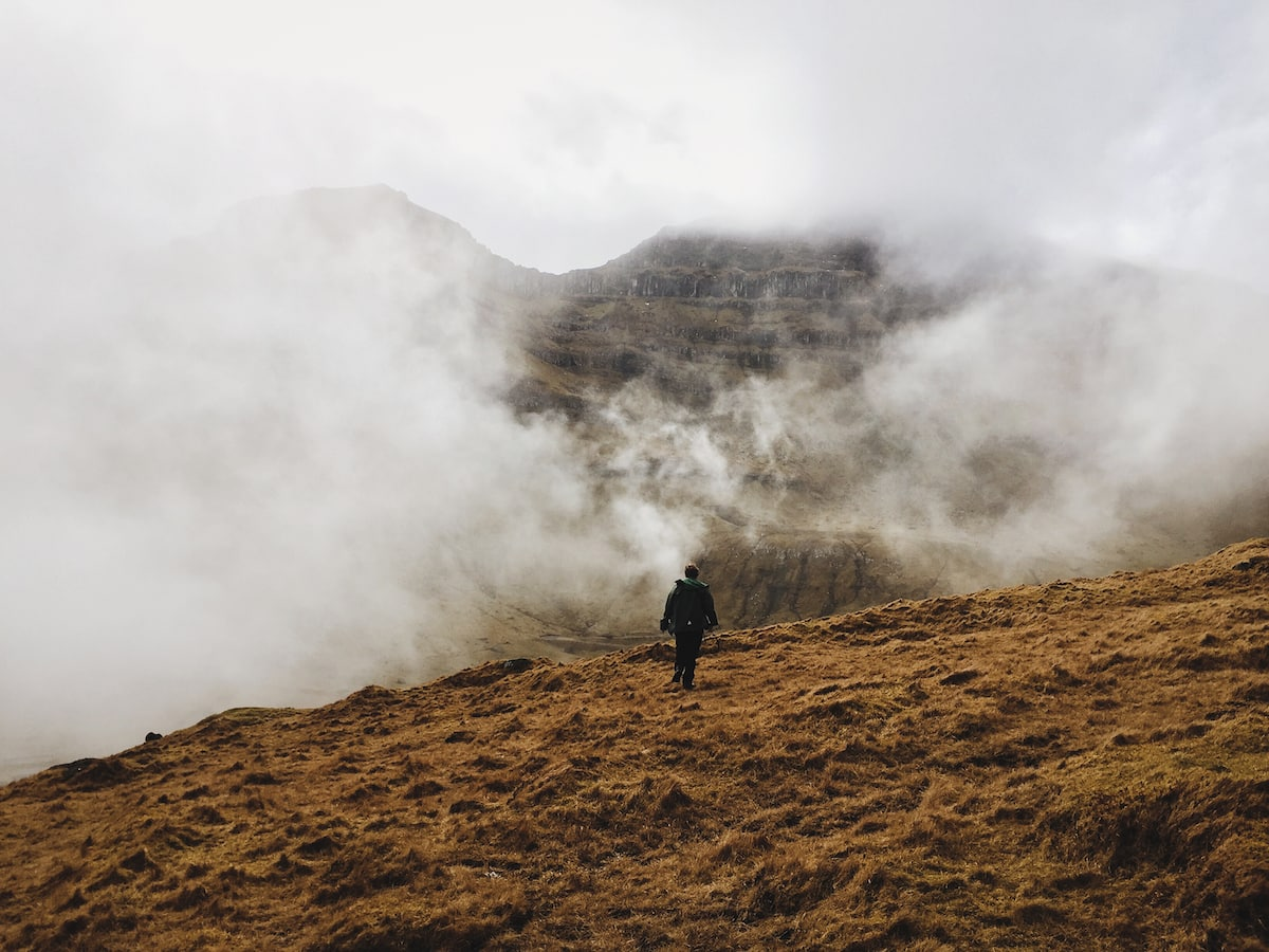 walking through the fog on kalsoy in trøllanes to get to the lighthouse in the faroe islands