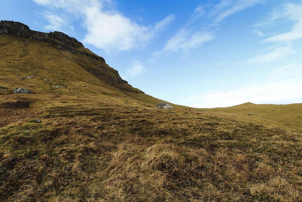 hiking through blue skies in the faroe islands in trøllanes to the kallur lighthouse on kalsoy island