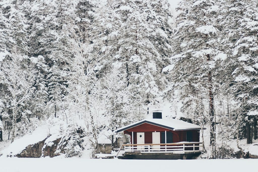 Nuuksio National Park: The Most Beautiful Winter Day Trip From Helsinki red house on frozen lake in forest