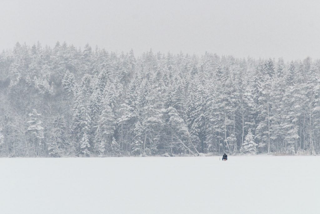 Nuuksio National Park: The Most Beautiful Winter Day Trip From Helsinki ice fishing on frozen lake