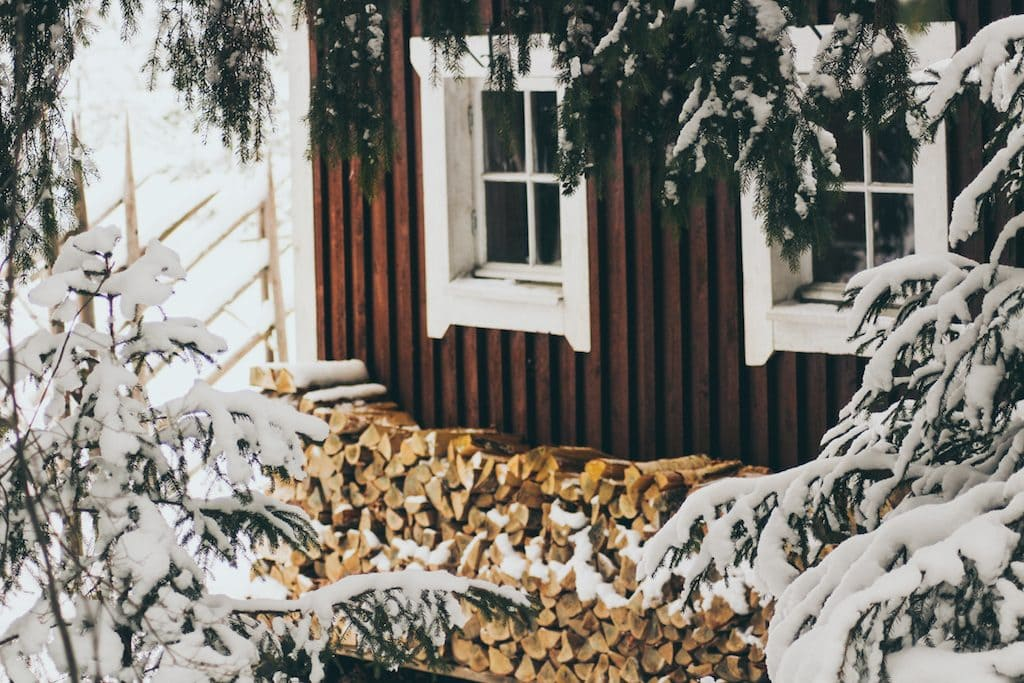 Nuuksio National Park: The Most Beautiful Winter Day Trip From Helsinki red house in forest with firewood