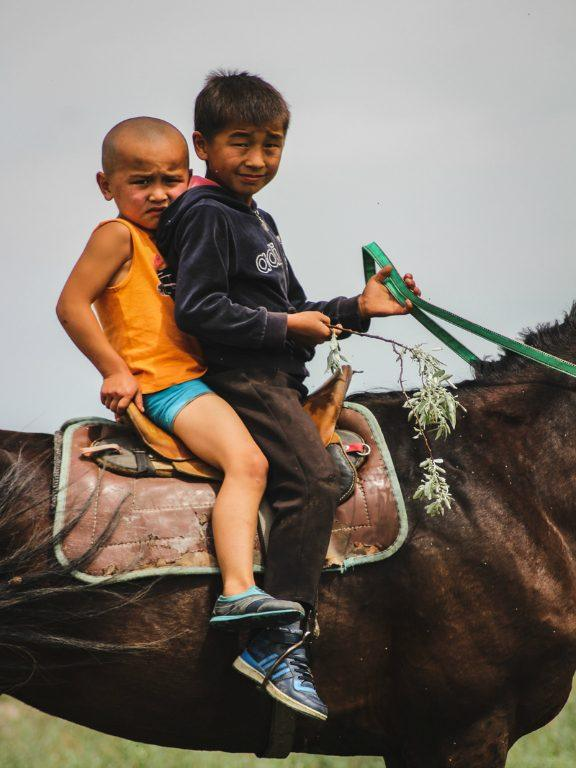 Central Asia Travel Tips: 50 Things to Know and Do Before You Visit kids on a horse in kazakhstan