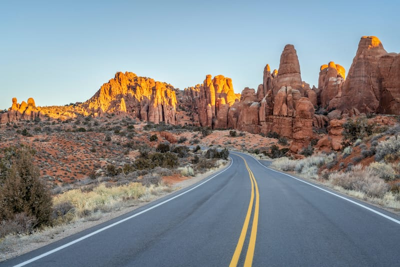 Winter sunrise driving on a highway through Arches National Park