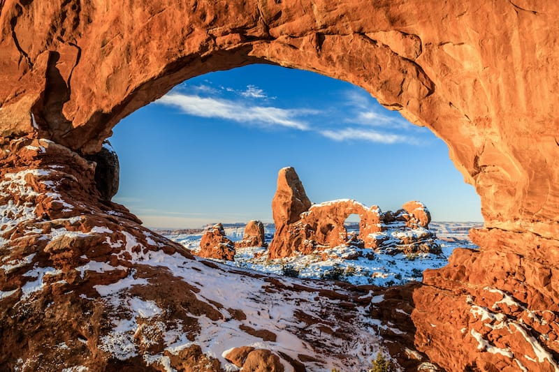 Sunrise of North Window Arch and Turret Arch after snow in Arches National Park in winter